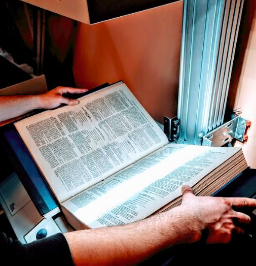 Best Way to Scan A Book - A picture of an operator scanning a large book